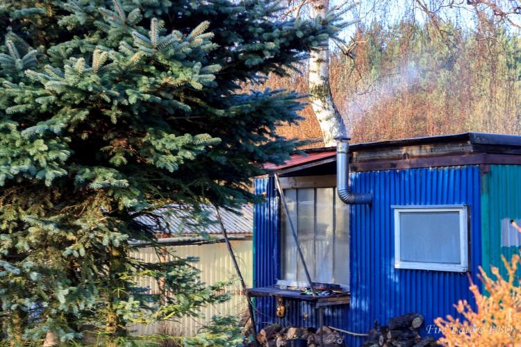 In unserer Räucherhütte qualmt einer der Räucheröfen von sich hin. Davor liegt gestapeltes Räucherholz.