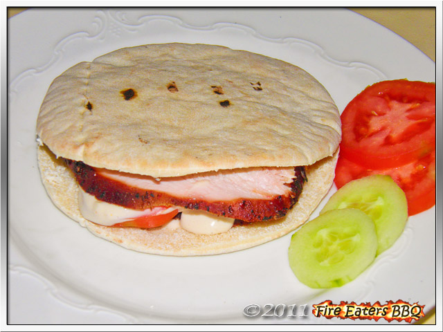 Ein Pastrami-Sandwich angerichtet mit Gurke und Tomate