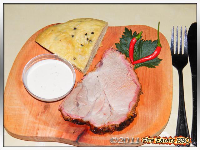 Ein Stück Schweinenacken aus dem Barbecue-Smoker mit Fladenbrot und Knoblauch-Dip.