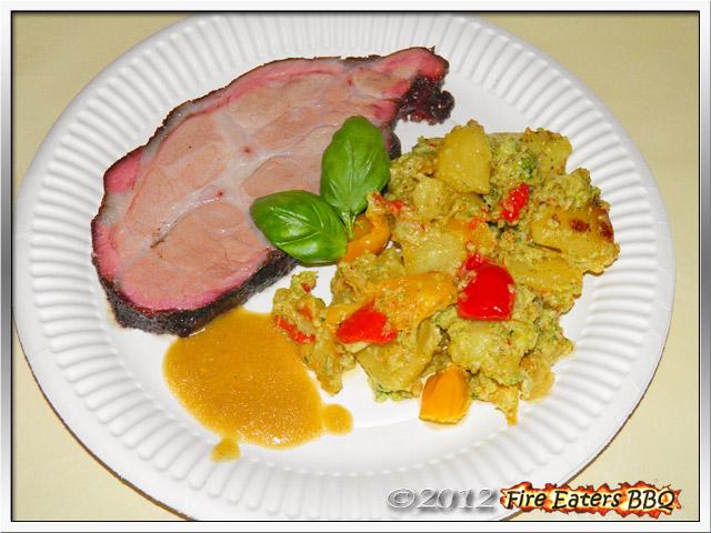 Ein Stück Schweinenacken aus dem Smoker mit einer fruchtigen Sauce und Salat