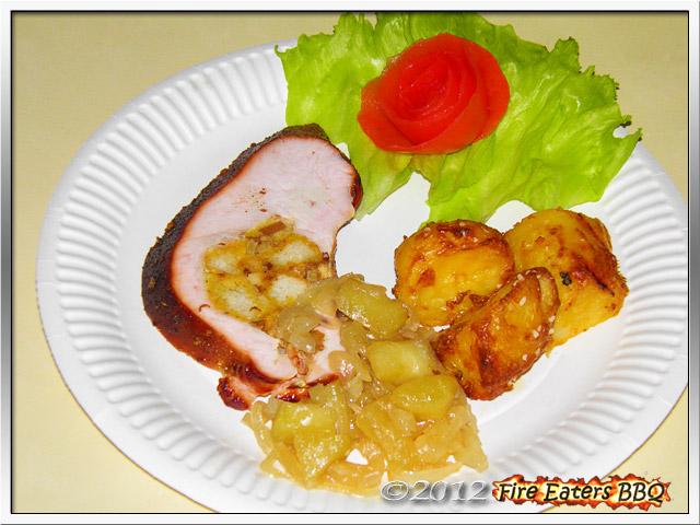 Eine Portion Putenbrust mit Semmel-Speck-Füllung angerichtet mit Kartoffeln und Zwiebelsauce